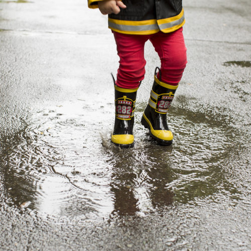 Rain boots splashing in puddle