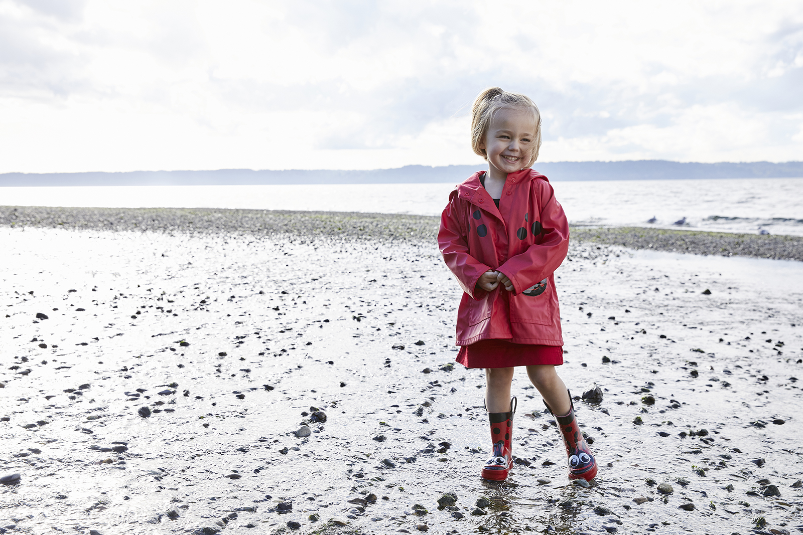 Girl in ladybug rain gear at beach