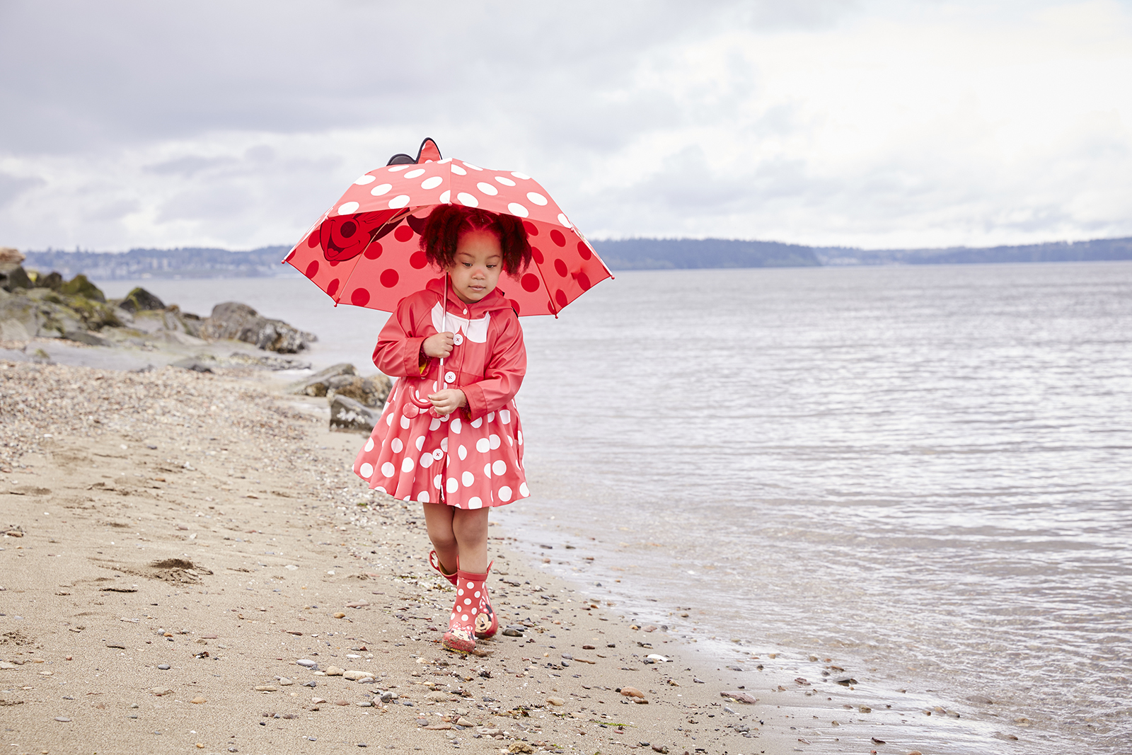 Girl in Minnie Mouse rain gear set at beach